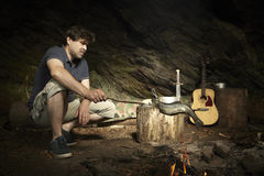 Man relaxing in wilderness and preparing hunted fish on fire. Man relaxing in wilderness with guitar and eating hunted fish stock photos