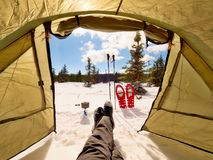 Man relaxing. Winter view from camping  tent entrance out. To snowy landscape. Travel Lifestyle concept, snow mountains. Hikers winter vacation Royalty Free Stock Images