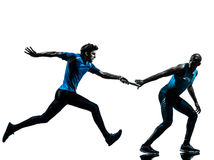 Man relay runner sprinter  silhouette. Two men relay running sprinting  in silhouette studio isolated on white background Royalty Free Stock Photo