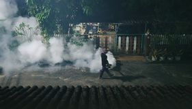 Man releasing smoke to clear up the mosquitoes and protect malaria in village at night stock photo