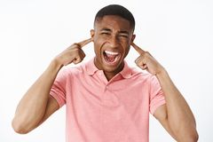 Man releasing stress cannot handle town noise. Displeased and fed up intense african american guy closing ears and. Shouting out loud, squinting being stock photography