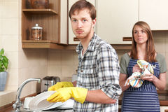 Man Reluctantly Washing Up In Kitchen With Partner Royalty Free Stock Photography