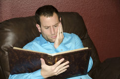 Man reminiscing looking at an old photo album. Royalty Free Stock Image