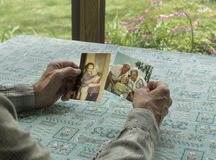 Man reminiscing with photos Stock Photo