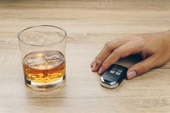 Man with a remote car key and a glass of bourbon whiskey stock image
