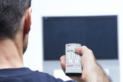 Man with remote control and flat tv Stock Photo