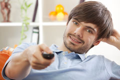 Man with remote control at home Stock Photo