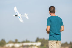 Man with remote control plane flying in air Royalty Free Stock Images