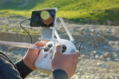 Man with remote control prepare white drone with digital camera for start flying in winter. Camera flying in sky over mountain Dro royalty free stock photography