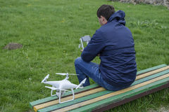 A man with a remote control quadroopter in his hands is sitting on a bench. White quadroopter prepare for flight. Royalty Free Stock Images