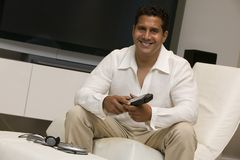 Man with remote control sitting in front of Large Screen TV in living room portrait Stock Photos