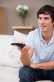 Man with remote control on the sofa Stock Photography
