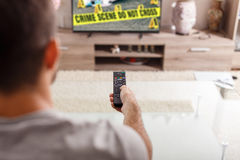 Man with remote control watching crime serie in TV Royalty Free Stock Photo