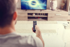 Man with remote control watching sci-fi at home Stock Photo