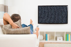 Man With Remote Control Watching Television Stock Photo