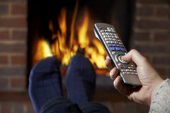 Man With Remote Control Watching Television And Relaxing By Fire Royalty Free Stock Photography