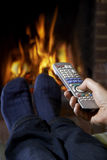 Man With Remote Control Watching Television And Relaxing By Fire Stock Photos
