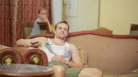 Man with remote control watching tv at home stock video footage