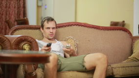 Man with remote control watching tv at home stock video