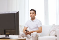 Man with remote control watching tv Stock Photography