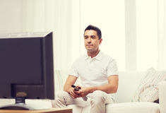 Man with remote control watching tv Stock Images