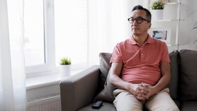 Man with remote control watching tv at home stock footage