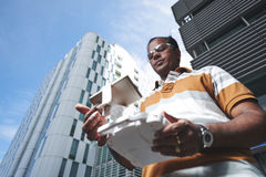 Man with remote controller against skyscraper. Low angle view of confident Indian man standing in front of modern skyscraper and holding drone remote controller Royalty Free Stock Photography