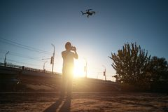 Man with remote controller operating flying drone or quad copter - modern small aircraft for aerial video making in city landscape stock images