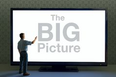 Man with remote and giant television saying The BIG Picture. Man pointing a remote at a giant TV television that saying The BIG Picture in huge text representing stock photos