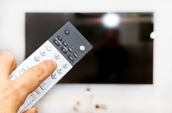 Man with a remote. Man using a tv remote Royalty Free Stock Photos