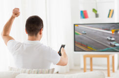 Man with remote watching motorsports on tv at home Royalty Free Stock Photo