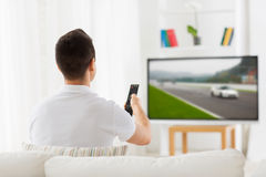 Man with remote watching motorsports on tv at home Stock Photos