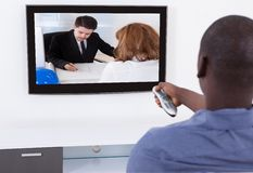 Man with remote watching television Royalty Free Stock Images