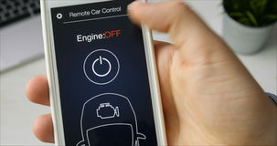 Man remotely starts engine of his car. Car remote control using smartphone application fictional interface. Using app on the smartphone stock footage