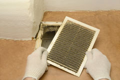 Man removes dust ventilation grilles. In white gloves Stock Images