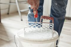 Man removes excess paint. From the paint roller stock images