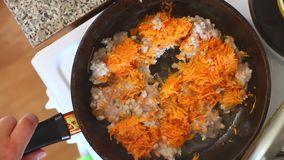 The man removes the lid from the frying pan, on which minced meat and chopped carrots. The man removes the lid from the frying pan, on which minced meat and stock video