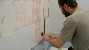 A man removes an old ceramic tile stock video footage