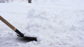 A man removes snow using a shovel stock footage