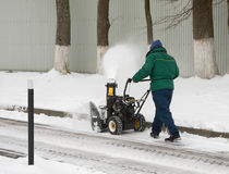Man removes snow by using a snow throwing machine. Snow removal from sidewalks and walkways with the use of small equipment stock image