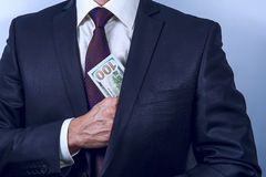 Man removes US dollars in his suit pocket stock photo