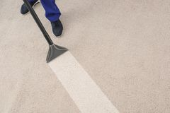 Man removing dirt from carpet with professional vacuum cleaner in room. Top view royalty free stock image