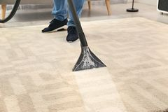 Man removing dirt from carpet with vacuum cleaner. In room royalty free stock photo