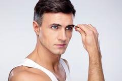 Man removing eyebrow hairs Stock Photo