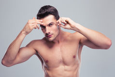 Man removing eyebrow hairs with tweezing Stock Photo