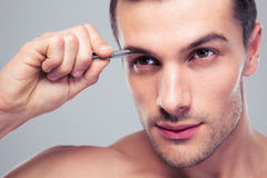 Man removing eyebrow hairs with tweezing Royalty Free Stock Images