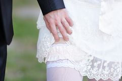 Man removing the garter from a married woman. Caucasian man removing the garter from a newly married woman Stock Photos