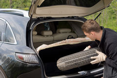 Man removing his spare tyre from the boot. Man removing his spare tyre from the open boot of his hatchback car after suffering a puncture on a country road Royalty Free Stock Images