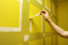 Man removing masking tape from wall Stock Photography