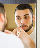 Man removing nose hair Stock Photos